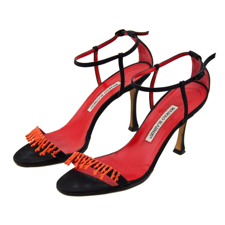Gorgeous Manolo Blahnik black suede strappy heels with red coral pieces along the toe strap. Red leather insole. Shoes marked a IT 38.5, shoe has been resoled. In excellent condition.