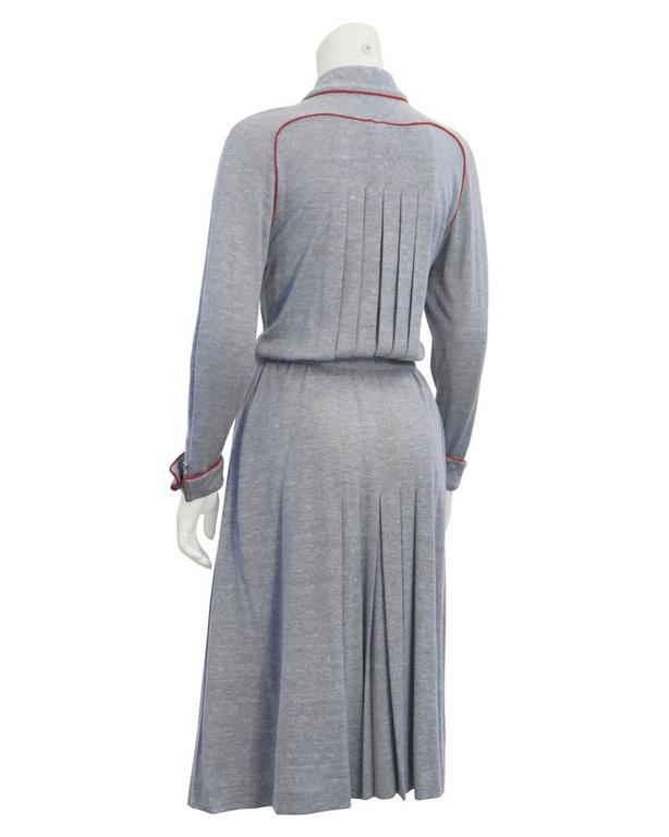 Elegant 1980's grey knit jersey Chanel day dress piped with deep red. Self tied neck bow, original gold CC logo buttons on pockets, sleeves and bow tie. Softly pleated skirt lined in silk, fitted waist enhances the blouse on look. Extra gold Chanel
