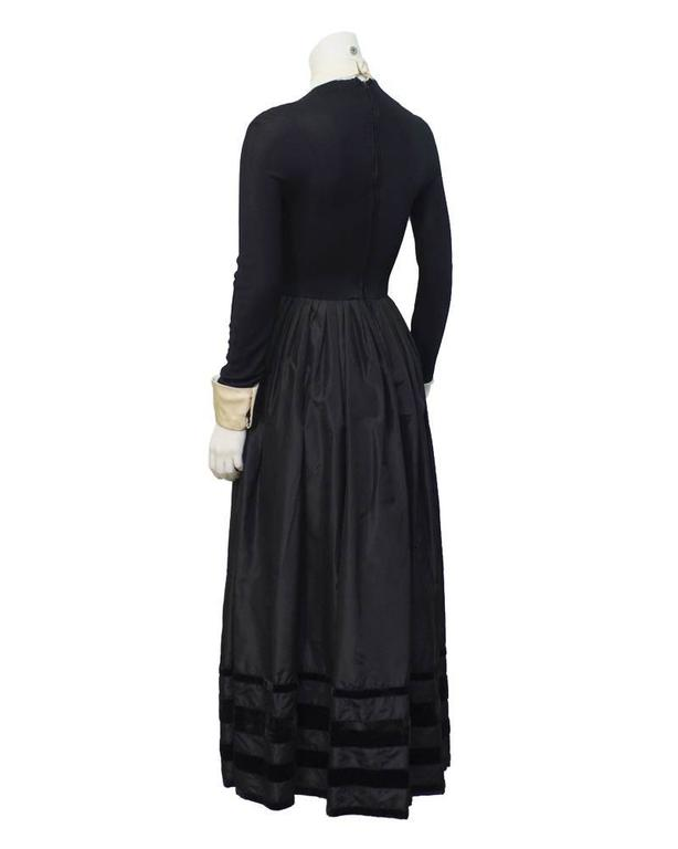 Black jersey and taffeta 1970's ingenue style evening gown with cream satin collar and cuffs. Fitted waistline attached to full taffeta skirt trimmed with velvet. In excellent vintage condition, fits like a US 4. One fabulous jewel at the neck is