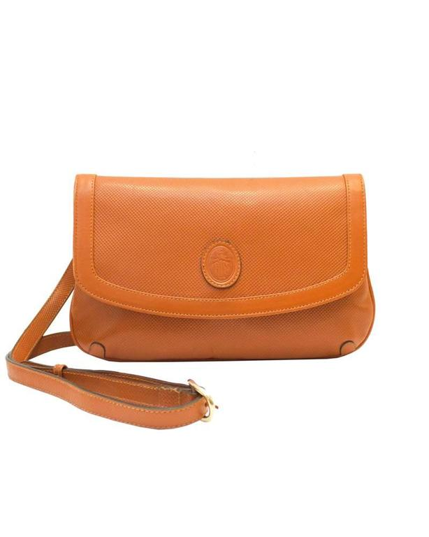 From the coveted handbag line by Mark Cross, this honey brown cross hatched leather clutch is great for everyday as it allows you to be hands free and fashionable! Dating from the late 1980's this bag has an adjustable long strap that can be removed