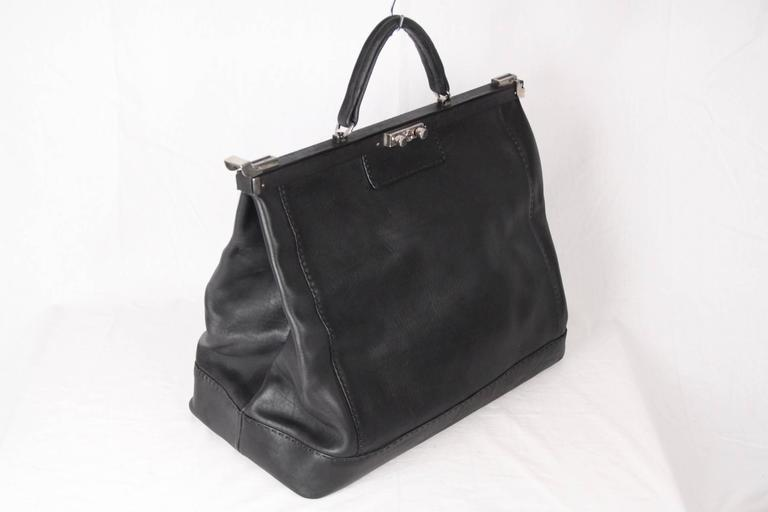 Oversized doctor bag,  weekender, carry on, or overnight tote bag, made in black genuine leather.  Framed top with lock closure on the front and side closures. Protective bottom feet. Inside, the bag has a removable pouch that can be which can also