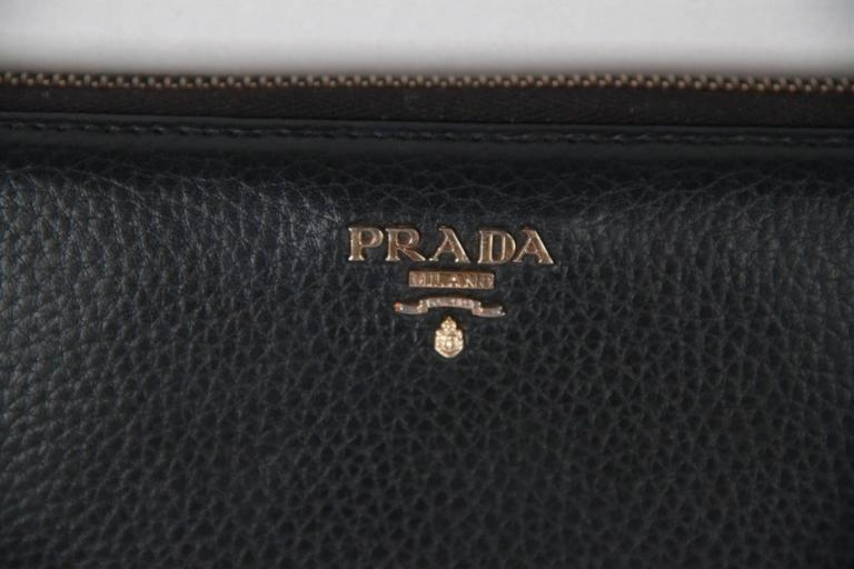 e8549d30ca182f Crafted of black leather, Prada's zip-around travel wallet includes a  pencil holder at