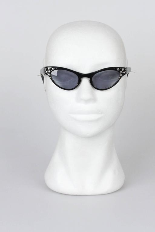 Unique vintage cat-eye sunglasses that are always timeless and always classy. Made with an acetate black based frame  with rhinestones and small golden studs detailing on corners, metal hinges and UV protected lenses. Made in France.  Style &