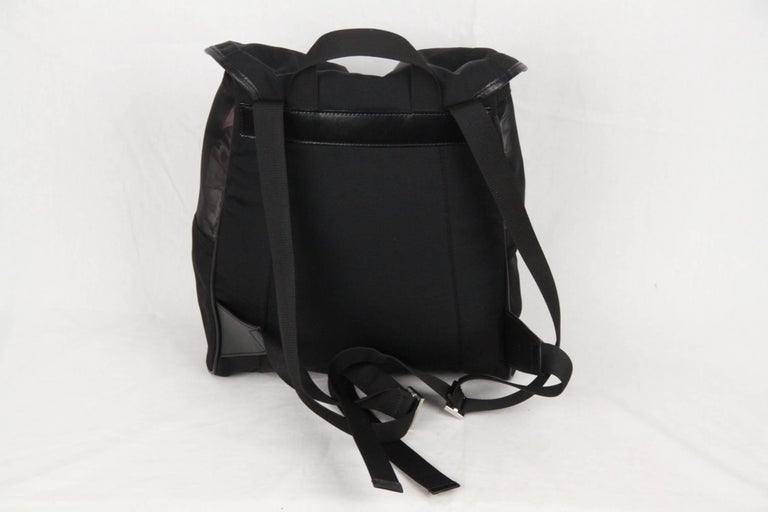 Gucci Black Canvas/Mesh Backpack Bag, featuring a sleek design with see-through mesh on the top sides and a canvas body trimmed with leather. Flap with velcro closure and top drawstring. Front zip pocket. Inside, signature lining and 1 side zip