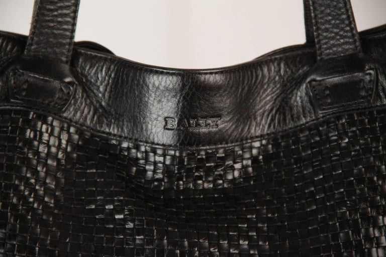 - Black Woven Leather panel on the front  - Double magnetic button closure - BALLY logo engraved on the front  - Fabric lining - Inside zip pocket   LOGOS & TAGS: 'BALLY' engraved on leather on the front, 'BALLY' tag