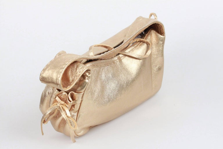 - PRADA gold tone leather shoulder bag  - Open top with self-tie closure  - Stitching detailing on the strap - Side pockets drawstring detailing - Beige satin lining - 1 side zip pocket inside - Measurements (HxLxD): 5.25 x 9 x 3.5 inches - 13,2 x