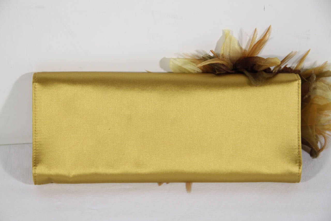 - Int. Ref. Numb.: AS287 - Gucci ANGELICA satin clutch in a shimmery yellow color - Maxi floral feather and organza appliqué - The GUCCI ANGELICA Clutch is part of the autumn-winter 2011/2012, inspired by '70s poster girl Angelica Houston -