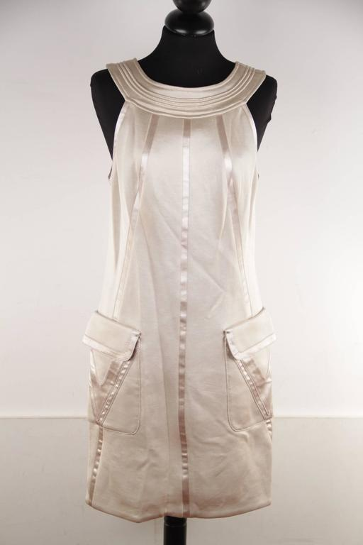- Versace Halter shift dress from the Fall 2006 collection - Beige color - Satin trim - Round neckline - 2 flap pocket on the hips - Composition: 77 % Viscose, 12% Nylon, 10% Acetate, 1% Elastan - Fully lined - Rear zip closure - Size : 42