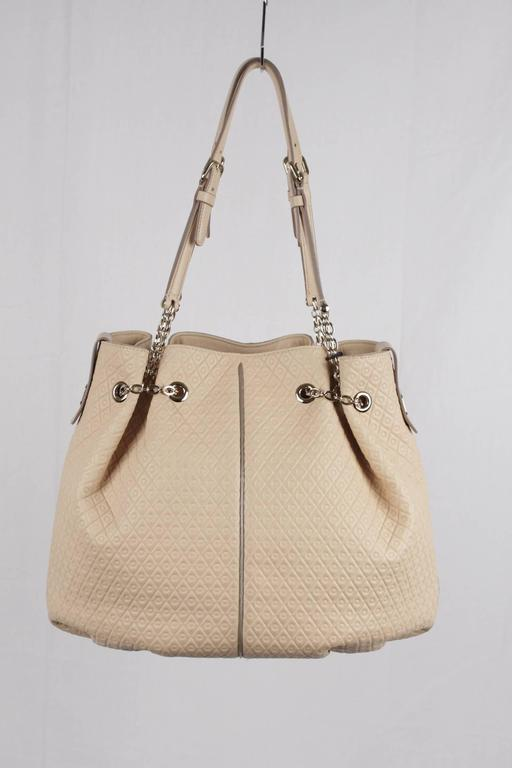 - TOD'S beige leather bucket shopper tote shoulder bag - Hand stitching - Embossed pattern - Gold metal hardware - 1 interior zip pocket - Open top with engraved snap tab closure - Dual straps - Protective feet - TOD'S name plate - Reatil
