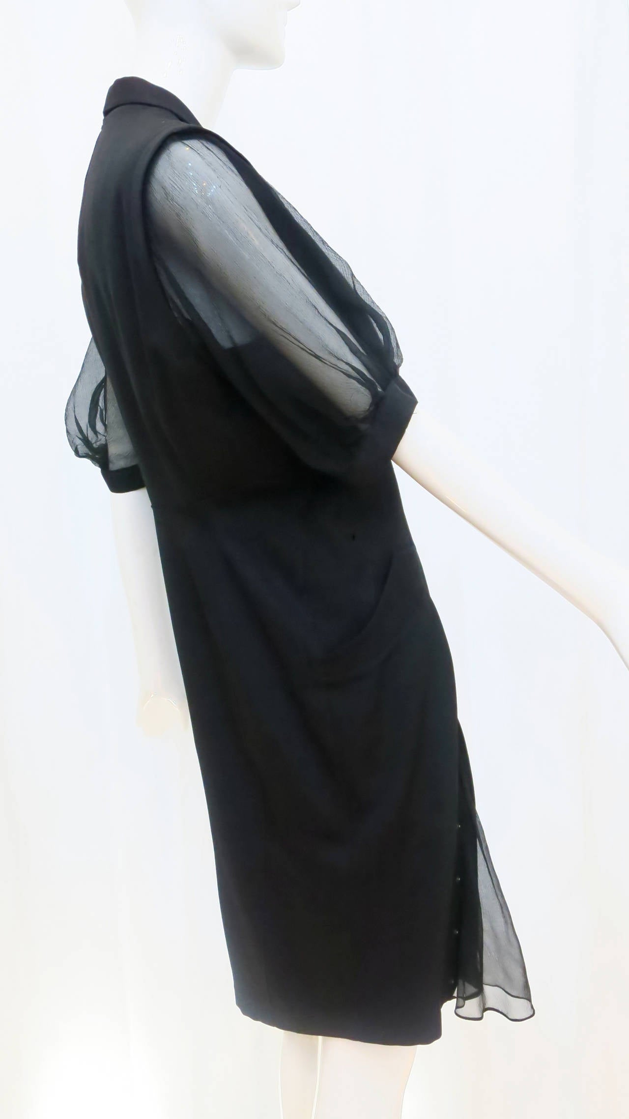 Showcasing his signature juxtaposition of sharp tailoring and sensual, revealing details, this Thierry Mugler shirt dress from the 1980s features sheer, billowy sleeves, a peek-a-boo sheer fabric panel at the thigh (which can be revealed or snapped
