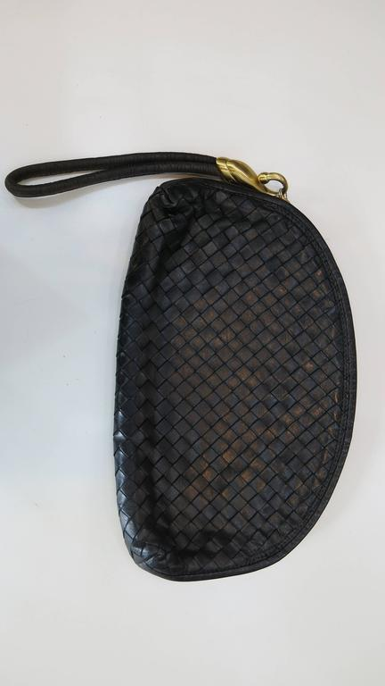 Black woven leather Bottega Veneta clutch. The bag appears virtually unused and features an inner zip pocket and an oversized leather pull as well as brass toned hardware. A classic night/day bag. The perfect size to carry the essentials and a
