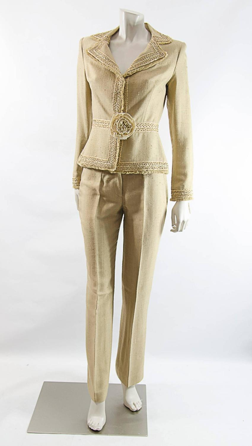 Look chic and fabulous in this R&M Richards pant suit. The fashionable suit features a jacket with shear, 3/4 length sleeves, elegant slacks, and a beautiful blouse with a beaded neckline.