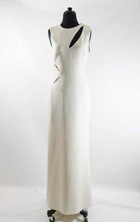 White silk-cady full-length sleeveless gown with cutout detailing at front, back and side. Versace gown has a thigh-high vent at side, round neck, flared skirt, is slightly fitted at the waist, has a concealed zip fastening at the side and is