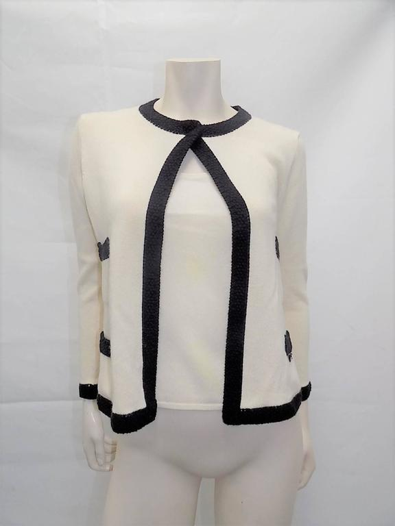 Collection 2003 in mint condition beautiful Chanel sweater set.  Ivory Cashmere with black crochet trim. Sleeveless top and sweater with one snap closure on the neckline. Four front patch pockets . Small Chanel plaque on the pocket. Size 40 Bust