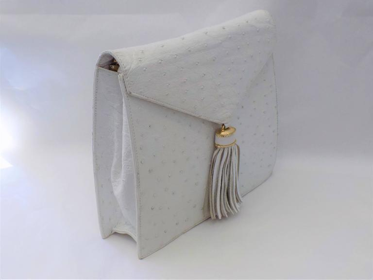 Beautiful SISO Vintage white ostrich envelope clutch  . Optional  shoulder bag with removable strap. Very clean and in good condition. .  Snap closure with tassel front. Mesures 8
