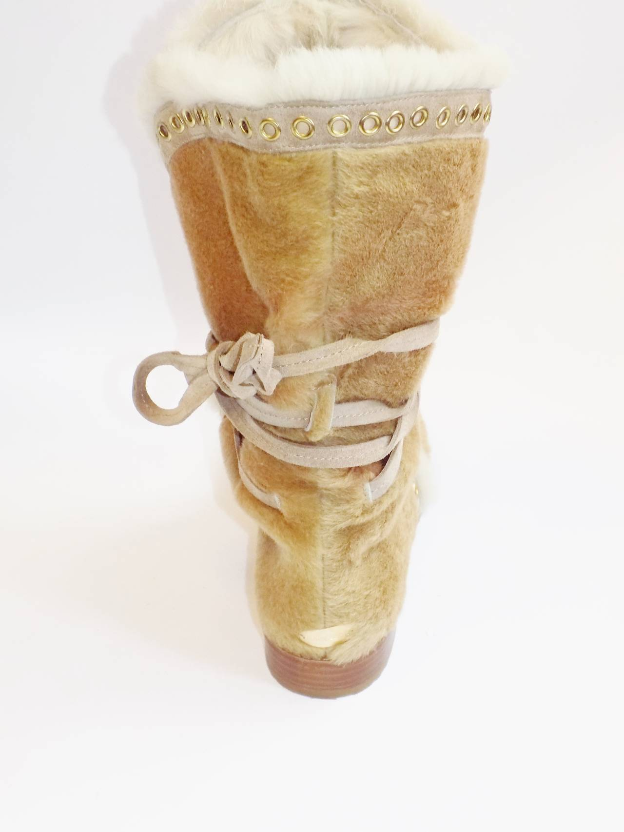 Tan pony hair boots with fur lining, suede trim with gold-tone grommets throughout and crisscross lace tie closures. 