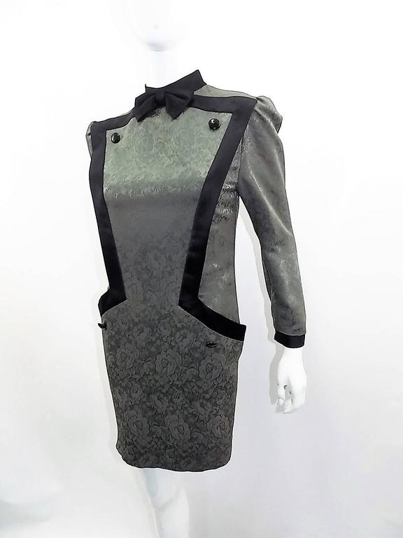 Circa late 1960's Vintage Nina Ricci dress .Wool and silk blend JACQUARD in satin finish. sage/ grey color with black details. Featuring front inserted pockets concealed by design, large black buttons and bow at the neckline.  Zipper back closure.
