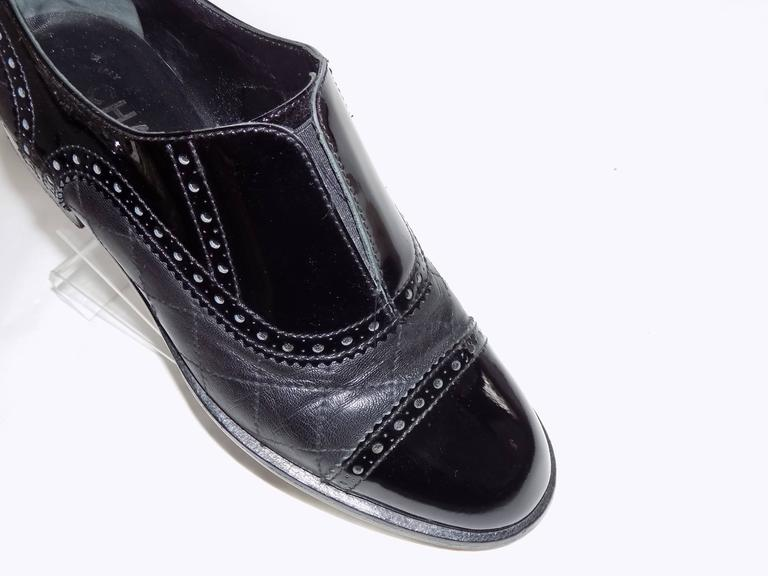 Classic and timeless Chanel Black Quilted Oxford Shoes . Combination of calf and patent leather with perforated trim. Easy to put on with elastic inserted under the front slit. . One inch stacked heel. . Small metal cc logo on the outer side of each