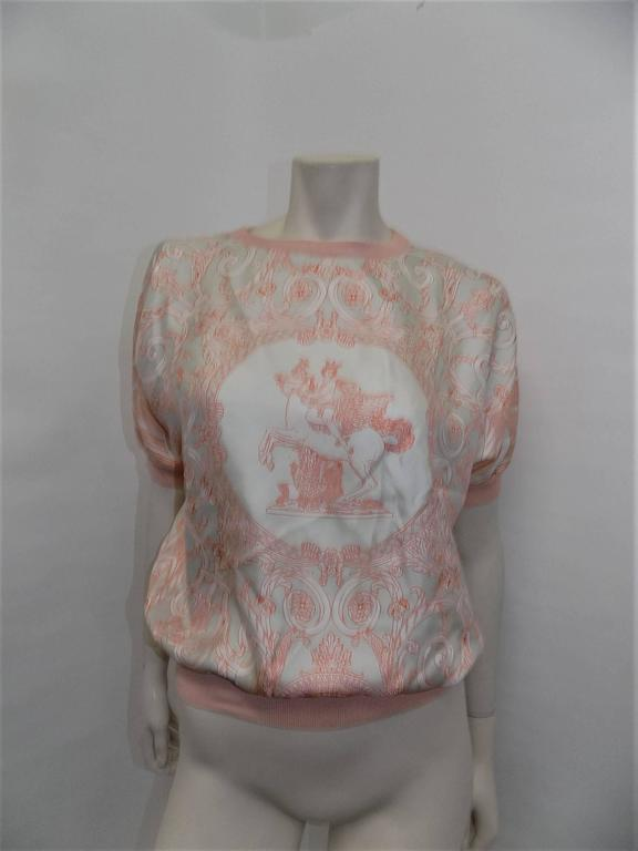 Spectacular and never worn pale peach blouse and cardigan set. Crew collared top with short sleeves and knit trim. Cardigan has double cuffs, gold toned buttons with Hermes Paris engraved details. Made in Italy. Top: 100% silk. Cardigan: 65%