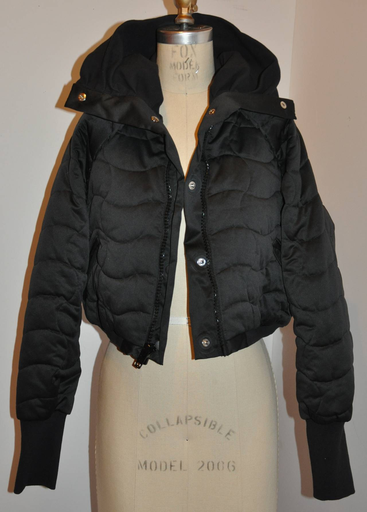 Stella McCartney wicked extreme high-collar black quilted cropped puffer zipper jacket has the options to use the interior snaps located underneath the front zipper. There are two front set-in pocket with detailed small flat pleats near the arms