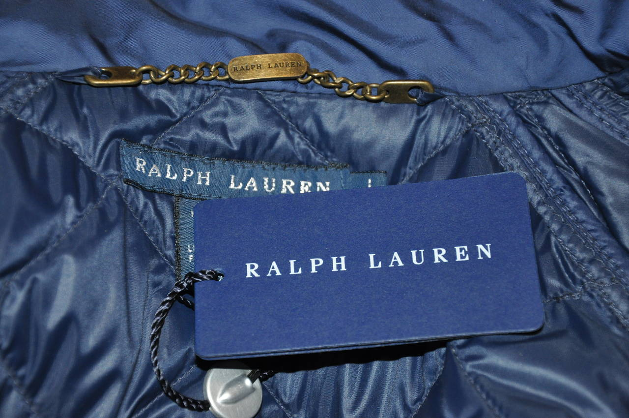Ralph Lauren wonderfully detailed navy quilted down vest has an optional matching belt with brass hardware if desired. Otherwise the vest can be worn without the belt. The front has a metal hardware zipper underneath the five front snaps along with