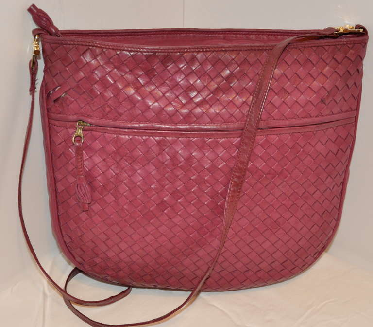 "Bottega Veneta classic woven lambskin leather in fuchsia measures 13"" in length, 12"" in height, 3 1/2"" in depth. Shoulder strap stands at 20"" in height. Bag has a zippered top accented with gold hardware along with thier classic lambskin tassle at"