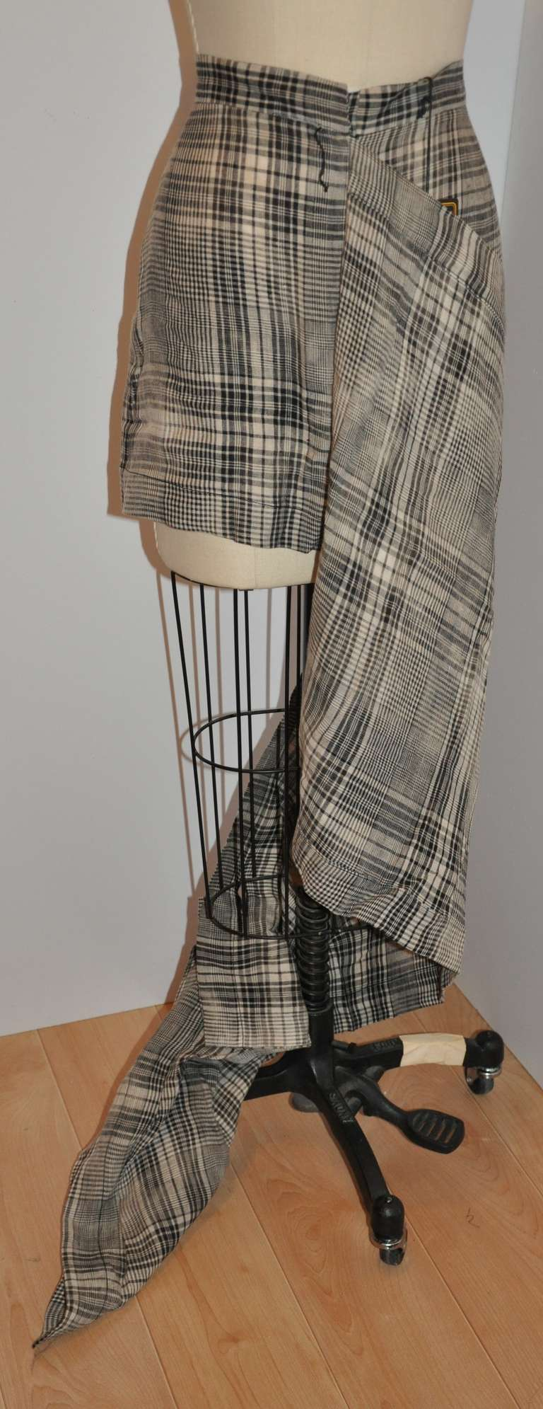 """Vivienne Westwood deconstructed black & white plaid skirt measures 15 1/2"""" in length on the actual skirt. The covering over-skirt measures 23 1/4"""". When the over-skirt is opened and laid flat, it measures 45"""" x 23 1/4"""", zipper is 6 1/4"""", waist is"""