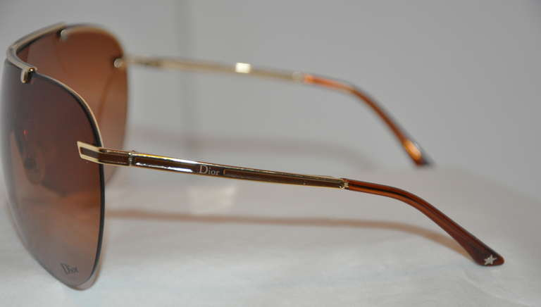Christian Dior wrap around sunglasses are accented with gilded gold hardware. The the center front-top is engraved with their signature name.    The height measures 2 1/2