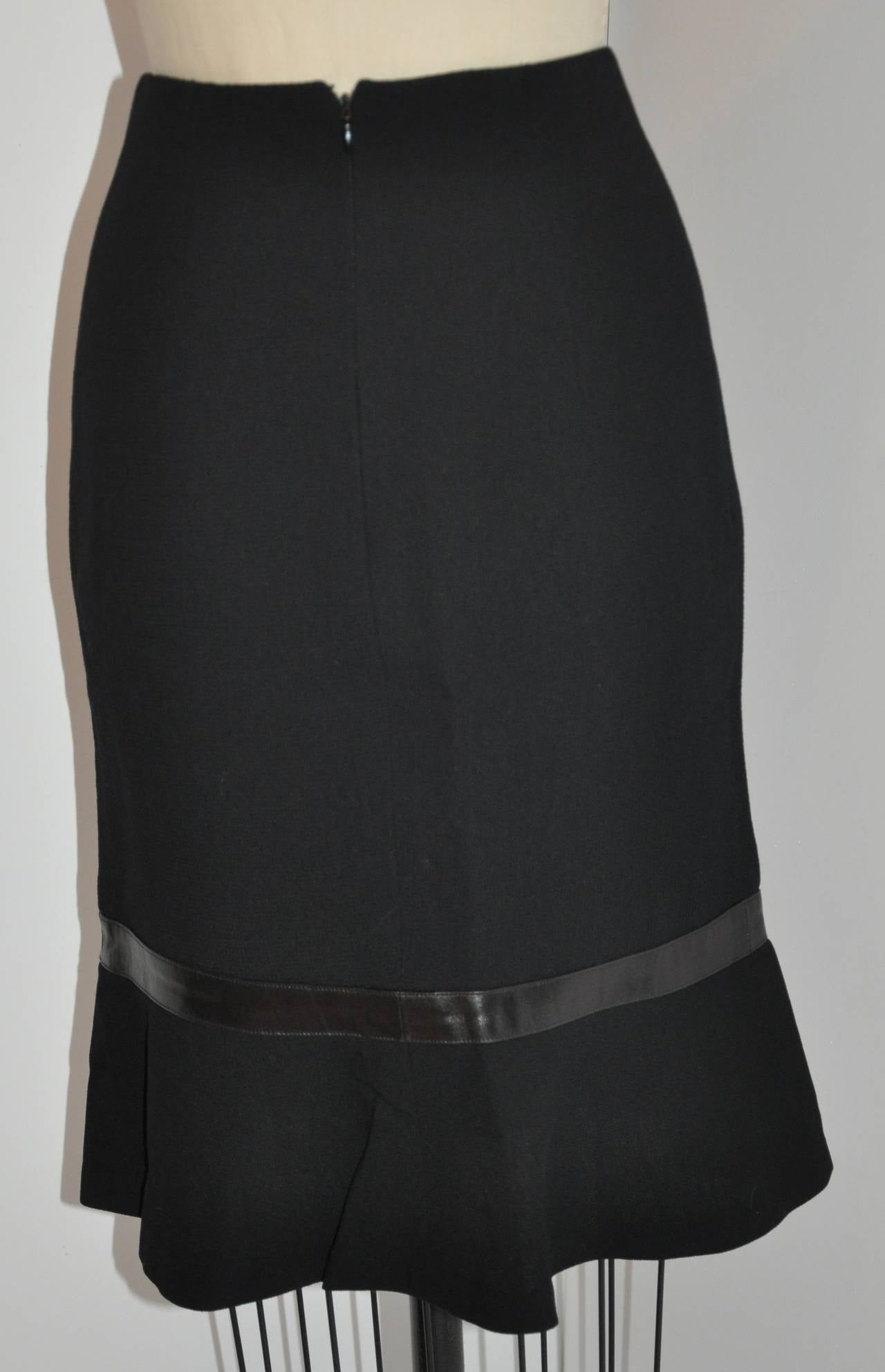 Luca Luca fully lined black wool crepe skirt accented with soft sheepskin leather toward the hem makes for a twist for a classic and elegant skirt.     Skirt is fully lined with black silk along with a center-back invisible zipper which measures 8