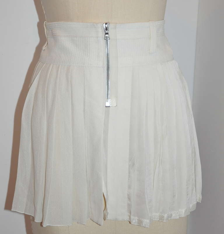 Marc Jacobs white silk pleated mini skirt features a zipper front which opens up so the skirt can lay flat when not in use, and for easier wear. The skirt is meant to be worn on top of the hips for a more whimisical look.