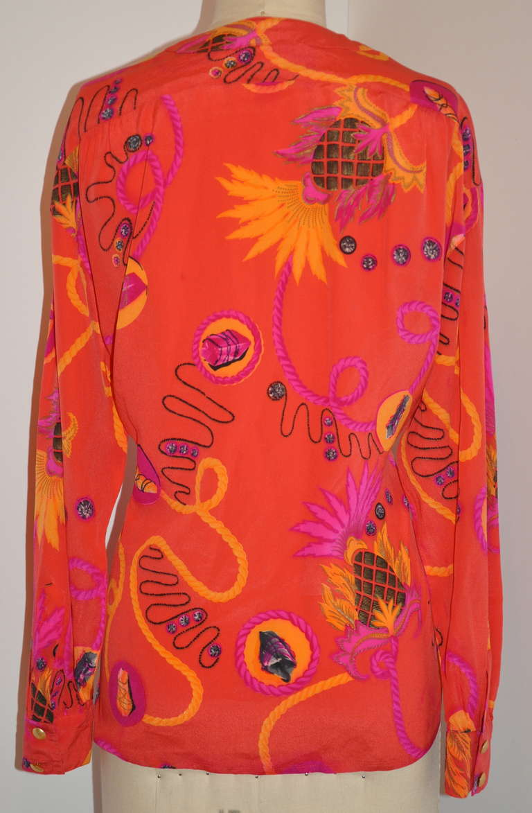 Escada by Margaretha Ley bold abstract tangerine with multi-color silk crepe de chine blouse is size 36/ West Germany.    There are six (6) buttons on front with slightly drop shoulders.    The front measures 23 1/2, back is 26 1/2
