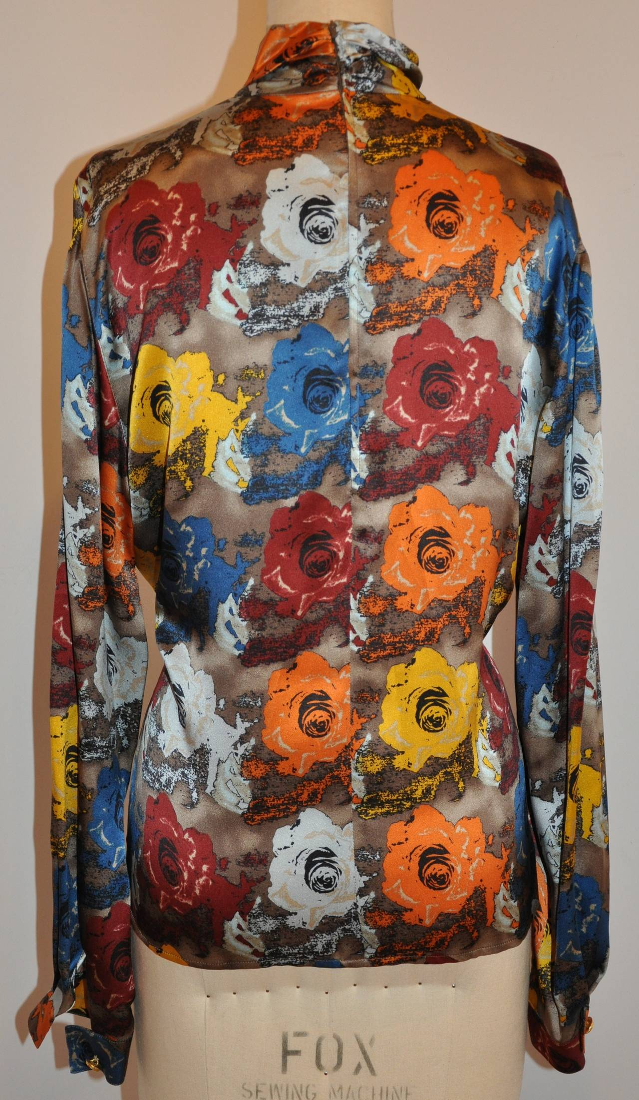 Emanuel Ungaro wonderfully elegant multi-color floral print high-neck silk zipper top is accented with gold hardware buttons on the sleeve's cuff.