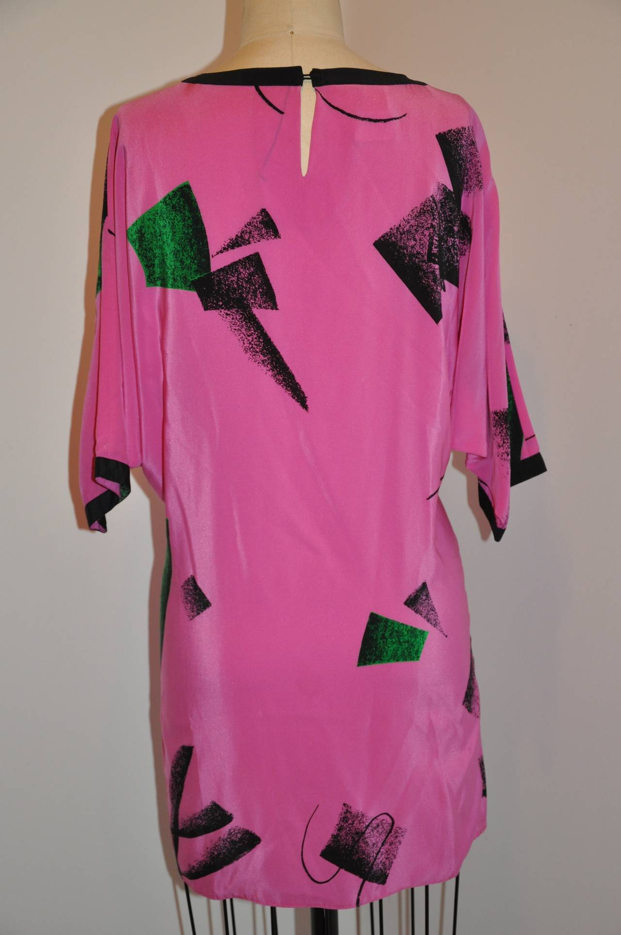 Flora Kung Bold fuchsia and Black abstract print silk tunic is accented with black along the neckline and sleeve's cuffs. The underarm circumference measures 46