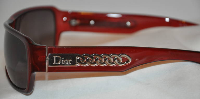 "Christian Dior burgundy/brown lucite sunglasses are accented with a ""chain"" accent on the arms, along with their signature nameplate.