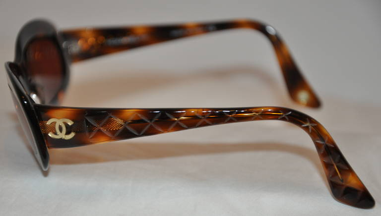 """This wonderfully detailed classic Chanel tortoise shell sunglasses has a gold hardware frame within with the tortoise shell overlay. The arms are detailed with bevel-quilted detailing.    The front measures 5 1/2"""" across the front, arms are 4 3/4"""""""
