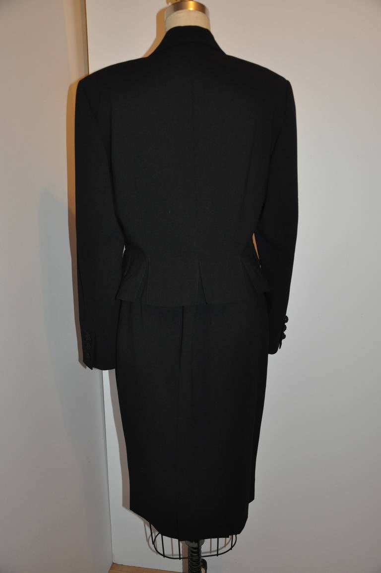 This wonderfully classic and elegant Guy Laroche 'Couture' black skirt suit is of polished spring wool and can be worn year-round. Fully lined with black silk on both the jacket and skirt. With hand-made silk cord covering each button involved.