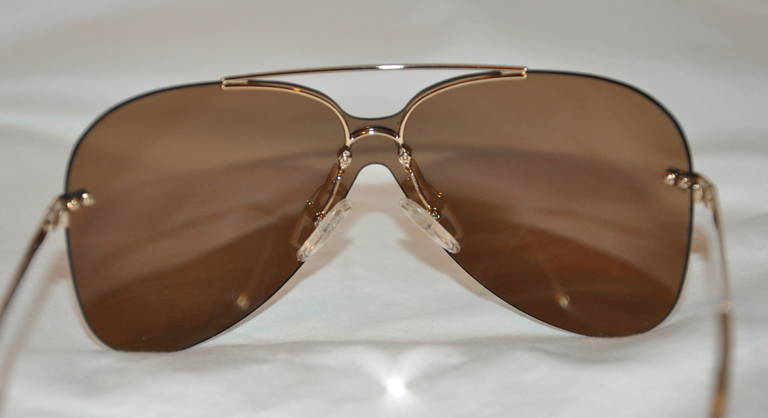 Christian Dior's polished gold hardware frame with gold mirrored lens are finished with clear lucite tips on the arms.