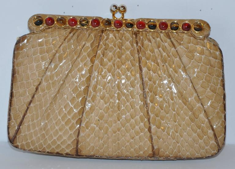 Judith Leiber's wonderfully detailed beige python evening clutch has the optional use of a evening shoulder bag with their removable straps of python and gold hardware. The evening clutch is highly detailed with tiger's eye and garnet