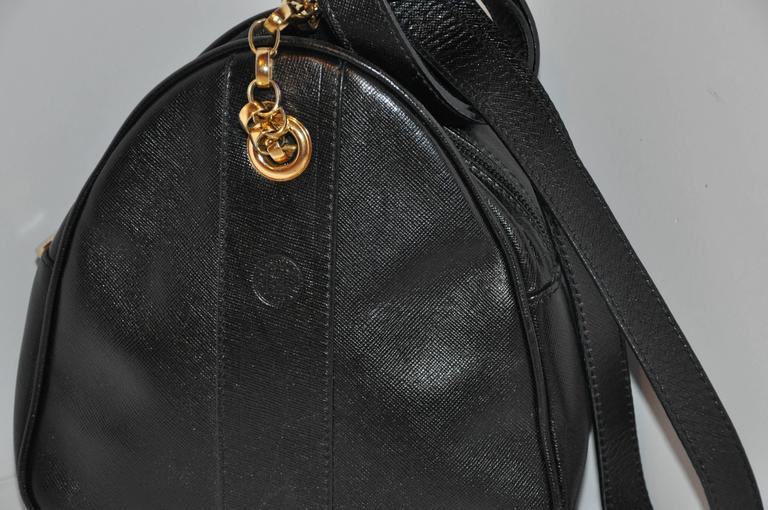 Fendi black textured calfskin leather small shoulder bag is accented with gilded gold hardware on the straps, eyelet and zipper's tab. Their signature name logo is located on the front-side.         The interior is fully lined and the top