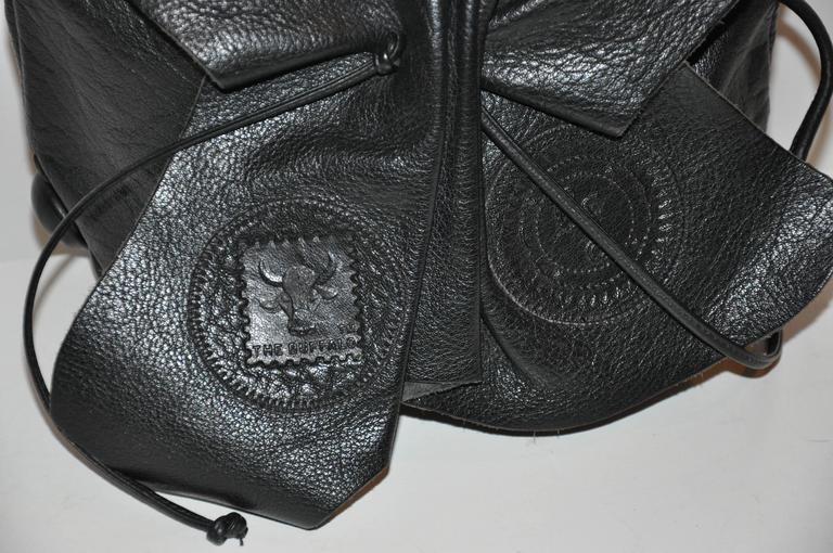 Carlos Falchi's signature black textured calfskin adjustable drawstring shoulder bag measures 9