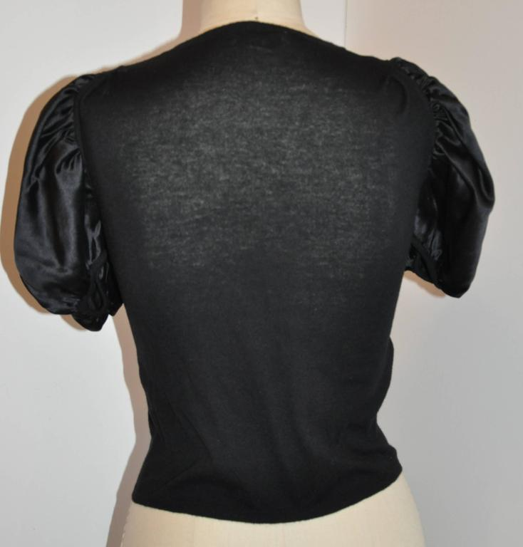 """Prada's wonderfully elegant black silk with wool & cashmere blend crew neck pullover top measures 11 across the shoulder. The underarm circumference measures 34"""", underarm-to-hem is 12"""", sleeve is 12, cuff circumference is 8"""", hem"""