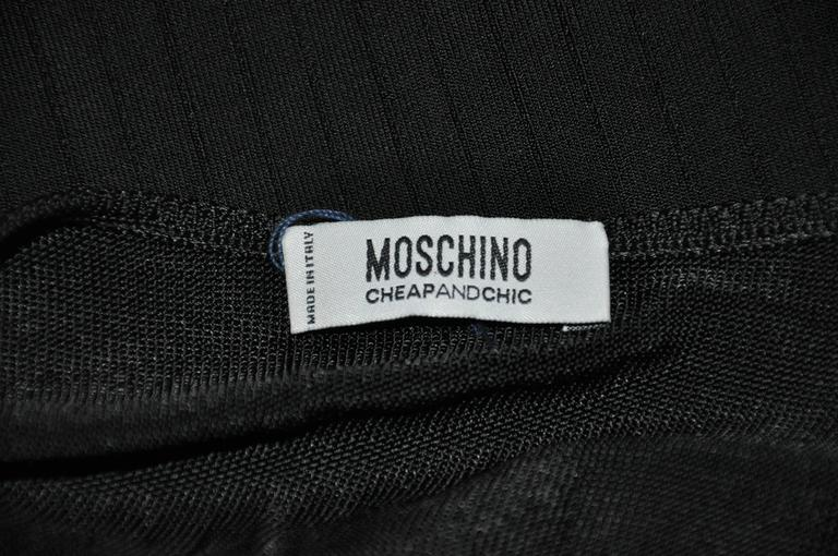 "Moschino wonderful sexy body-hugging black stretch knit tank top is detailed with micro-lace hem-line. The length of the front measures 9 1/4"", back is 18 3/4"", underarm circumference is 32"", shoulder is 11"" across, underarm-to-hem is 12""."