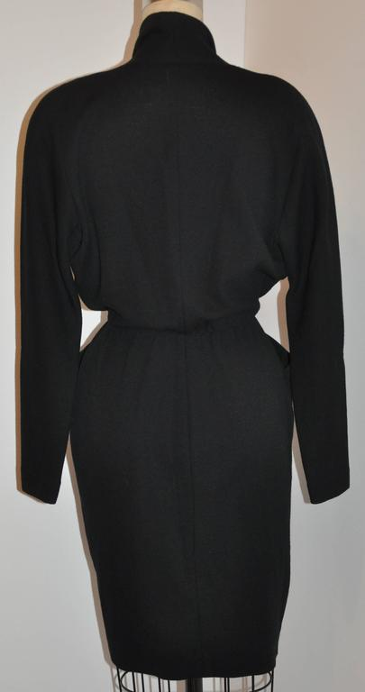 "Donna Karan's iconic signature ""Sold Out"" black wool crepe deep-front jersey dress sold out in a matter of hours when she first presented this wonderful collection. A perfect dress to pack for traveling, and easily can be worn from day"