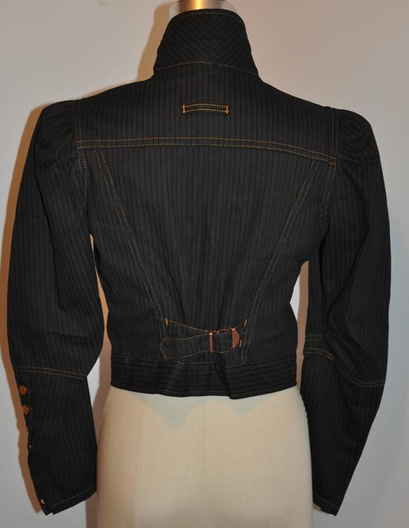 Jean Paul Gaultier cropped jacket is accented with detailed tapered sleeves accented with snaps at the cuffs and puffed shoulders. The center back has adjustable pulls to tighten if desire. There are two patch breast pockets with snap flaps.