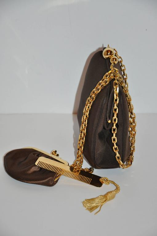 Judith Leiber wonderfully whimsical yet elegant textured coco-brown silk evening shoulder bag is accented with vermeil-finished gold hardware. The fully lined interior is paired with a gold hardware comb which is accented with a tassel as