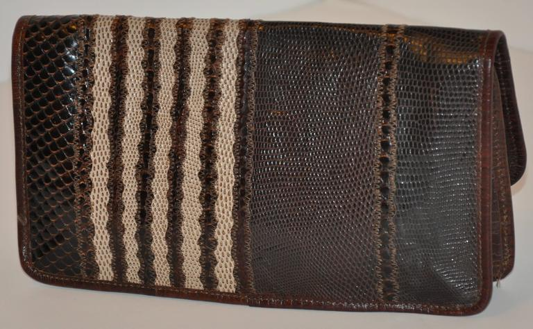 As only Carlos Falchi can, This wonderful multi-texture combination of lizard, snake and pylon skin finished with lambskin leather piping along the edges as well as the interior lining with shades of coco brown and browns. This wonderful