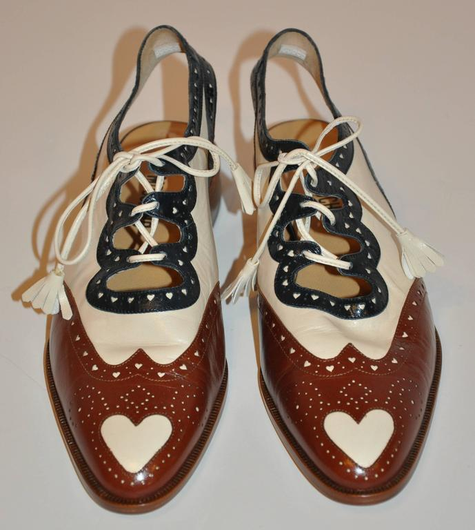 """This wonderfully detailed and well made multi-colors of navy, beige and brown s accented with tiny """"heart"""" eyelets throughout as well as one large """"heart"""" in front. Made of calfskin leather, the tie laces are of the same and finished with"""