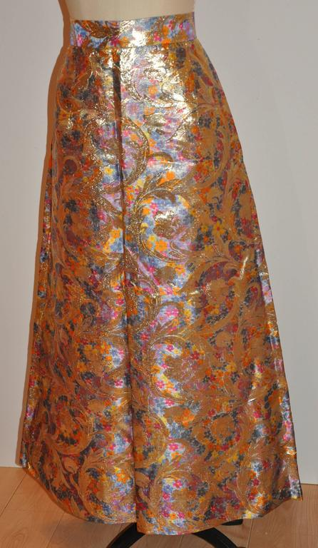 "This wonderfully elegant silk brocade floral flare maxi skirt is accented with elaborate gold lame floral weave as well. The waistband width measures 1 7/8"", waist is 30"", hips are 49"", length is 39 1/2"", hem circumference is"