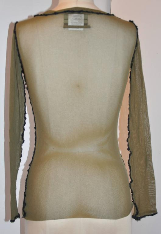 """Jean Paul Gaultier stretched olive green netted accented with black embroidered pullover top has a slight 'boat-neck"""" neckline which measures 20"""" in circumference. Shoulder are 14"""" across, length is 24"""", sleeve is 23"""","""