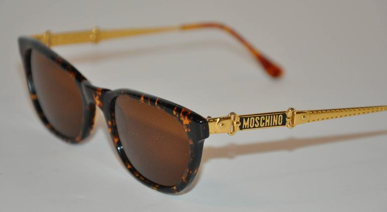 Moschino wonderfully detailed tortoise shell sunglass are engraved with the signature name-plate on both the exterior as well as the interior of both arms. The arms are also detailed with gold-tone engraved buckle and belt accents. The front